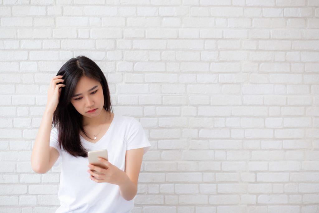 アプリ選びに悩む女性