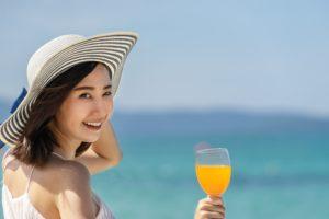 海をバックにジュースを飲む女性