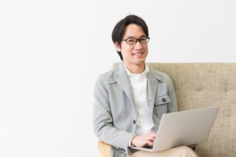 パソコンを膝の上に置く50代男性