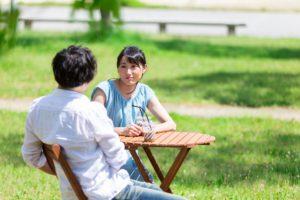 カフェの野外席で会話をする男女