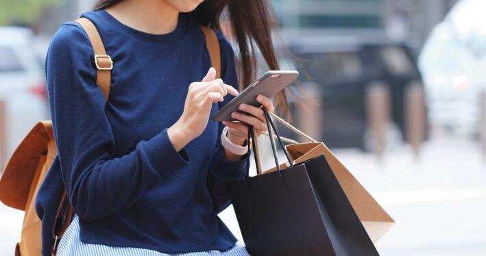 買い物しながらスマホを操作する女性