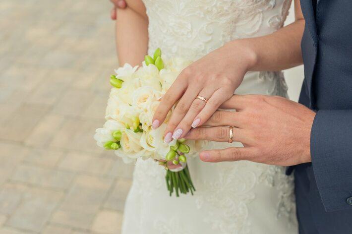 ウェディングドレス姿で手を触れ合う新郎新婦
