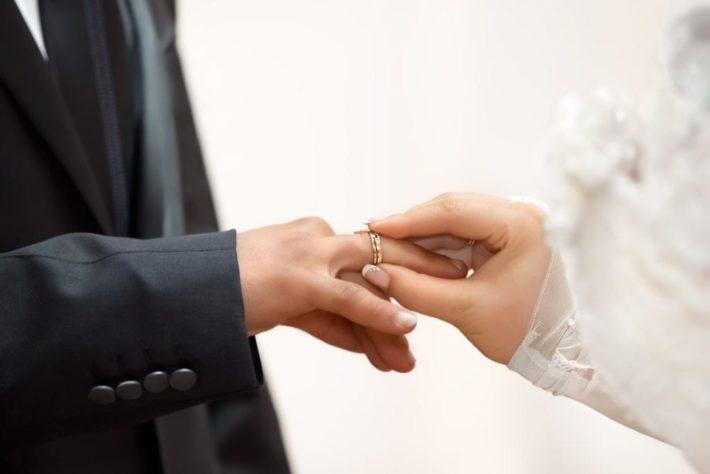 新郎に結婚指輪をはめる新婦