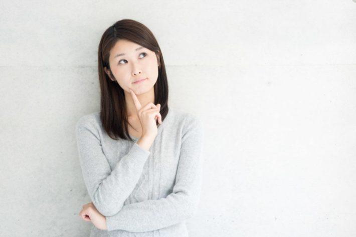 腕を組み疑問の表情を浮かべる女性