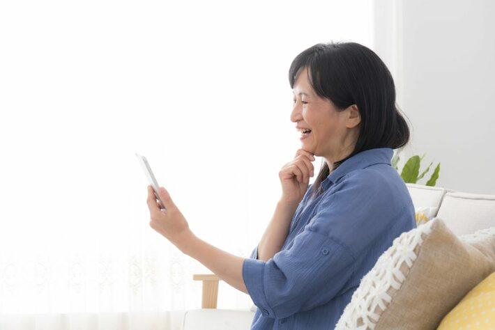 スマートフォンを見る60代女性