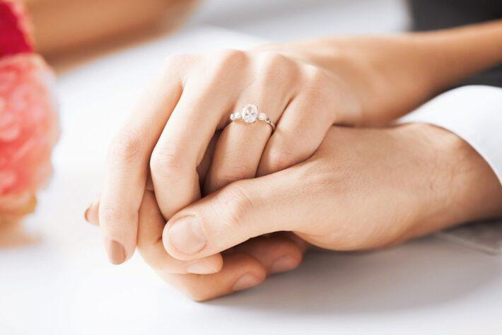 結婚指輪をして手を重ねる夫婦
