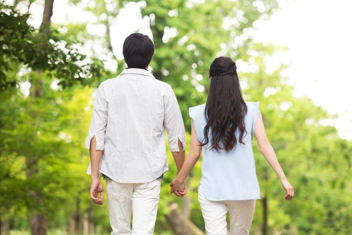 手を繋ぎ歩くカップルの後ろ姿