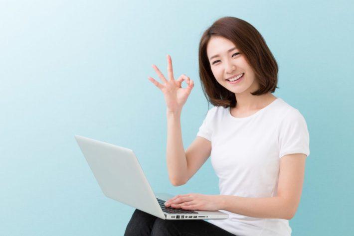 パソコンを膝にのせ手でOKマークを出す女性