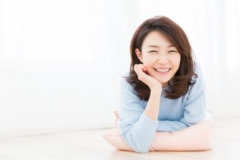 笑顔でほおづえをついている女性