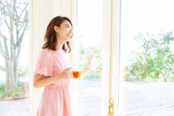 紅茶を片手に持ち窓の近くでたたずむ女性