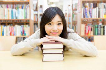 本の上に顔を載せている女性