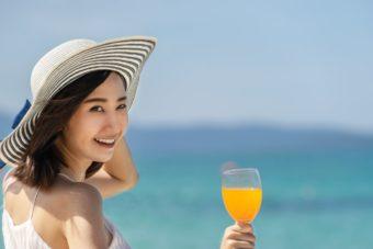 海辺で麦わら帽子を被りドリンクを持つ女性