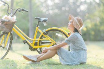 自転車の横で座る女性