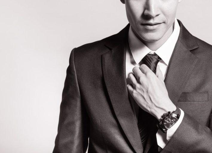 ネクタイを整えているスーツの男性