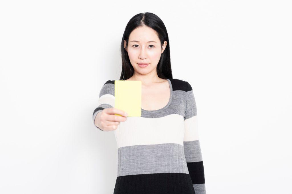 イエローカードをかざす女性