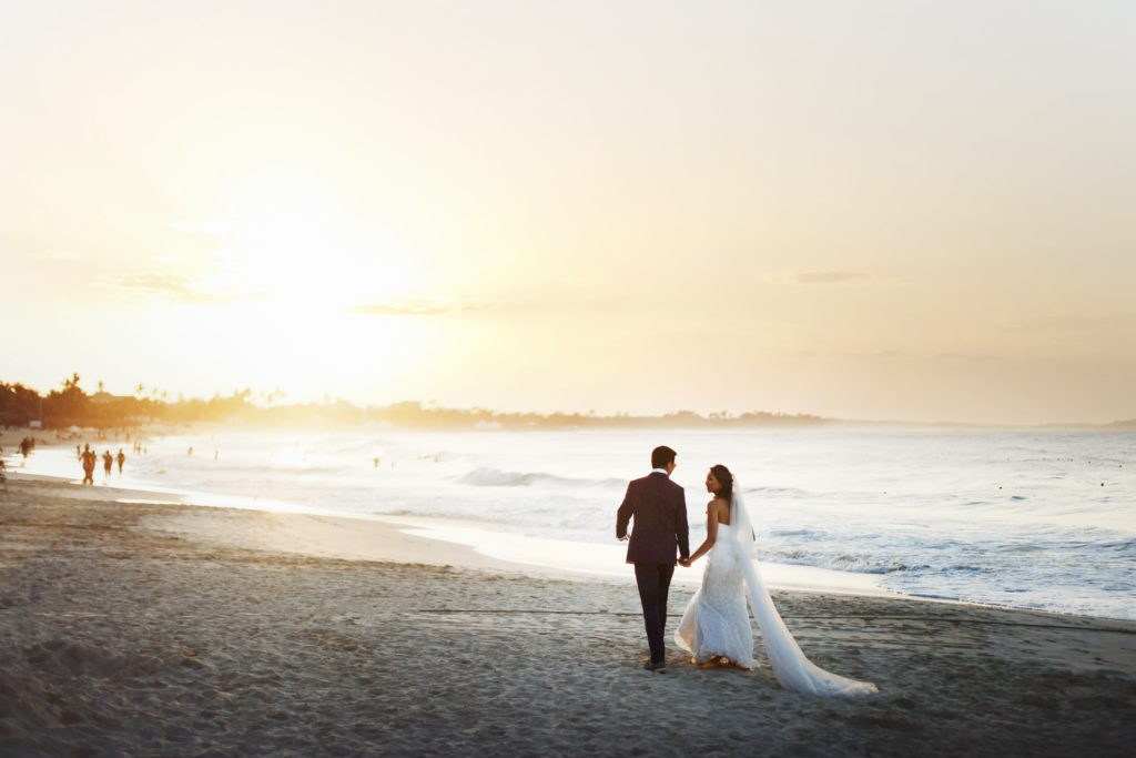海辺を歩く結婚男女