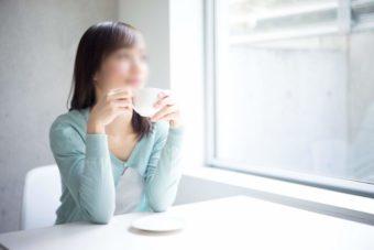 カップを持ち窓の外を眺める女性