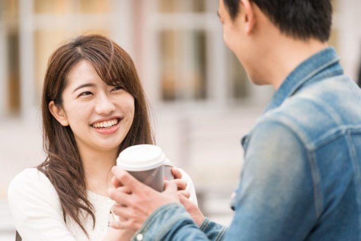 笑顔で男性からコーヒーを受け取る女性
