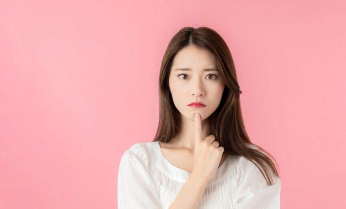 顎の下に指を置いて疑問気な表情を浮かべる女性