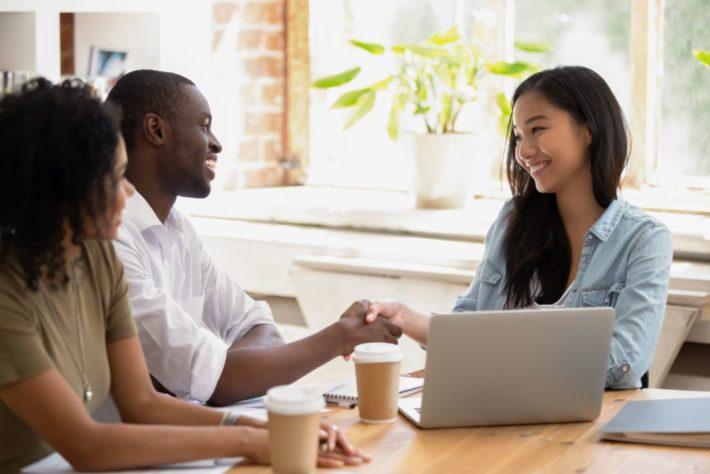 カフェで黒人と握手をするアジア人女性
