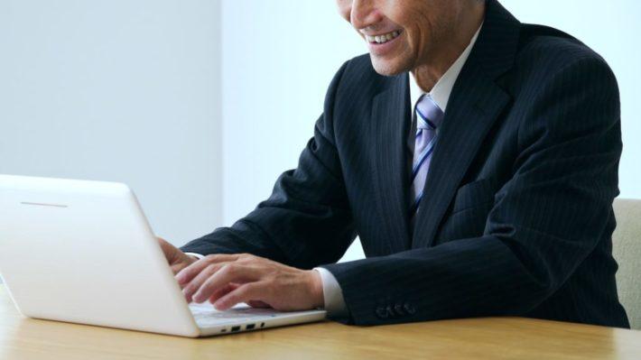 怪しい表情でパソコンを操作する男性