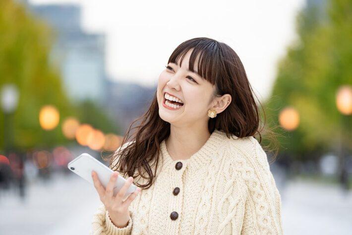 スマートフォンを持ち笑う女性