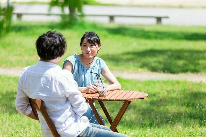 外で男性とお茶を楽しむ女性