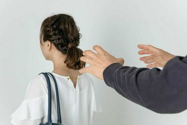 女性の背後から迫りくる怪しい手