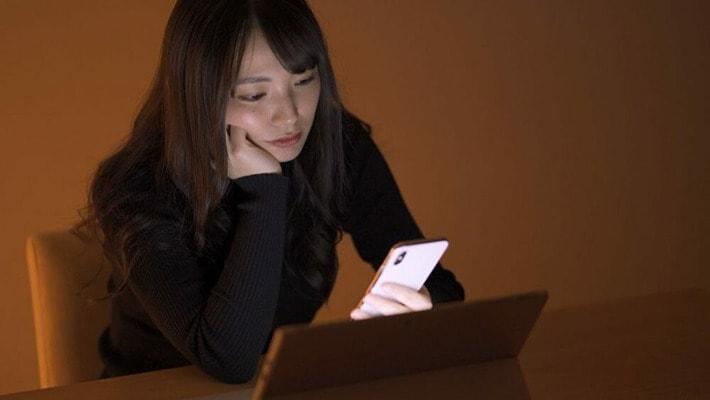 暗い部屋でスマートフォンを見ている女性