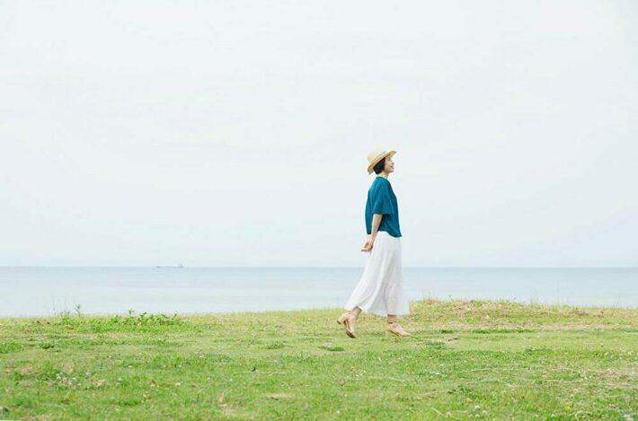 麦わら帽子を被って散歩する女性