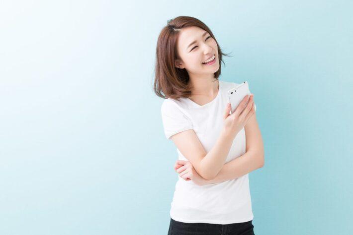 笑顔でスマートフォンを持つ女性