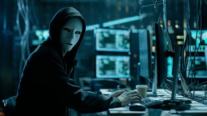 仮面を被りコンピューターを操作する怪しい人物