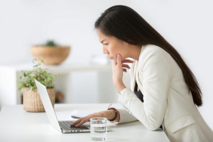 パソコンを見ながら顔をしかめる女性
