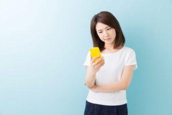 スマートフォンを見て不審な表情を浮かべる女性