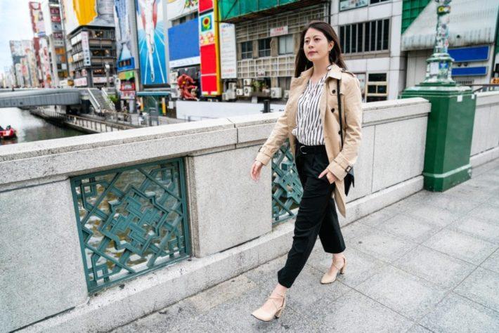 ビジネスカジュアルの恰好で街を歩く女性