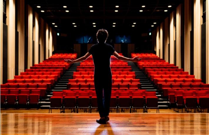 舞台の上で両手を広げる男性