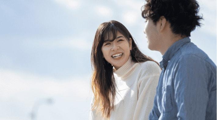 笑顔で隣の男性と話す女性