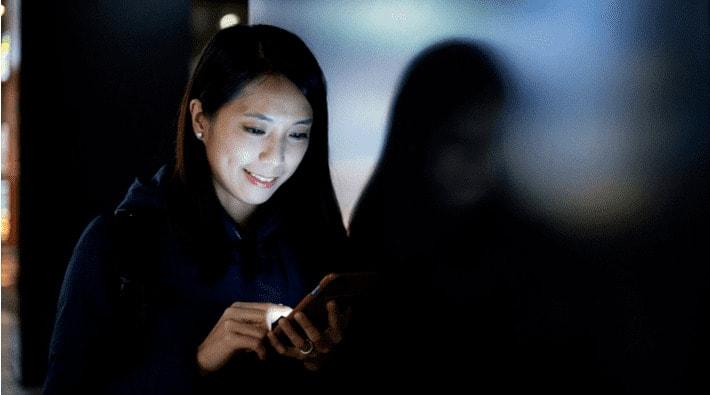 暗闇でスマートフォンを操作する女性