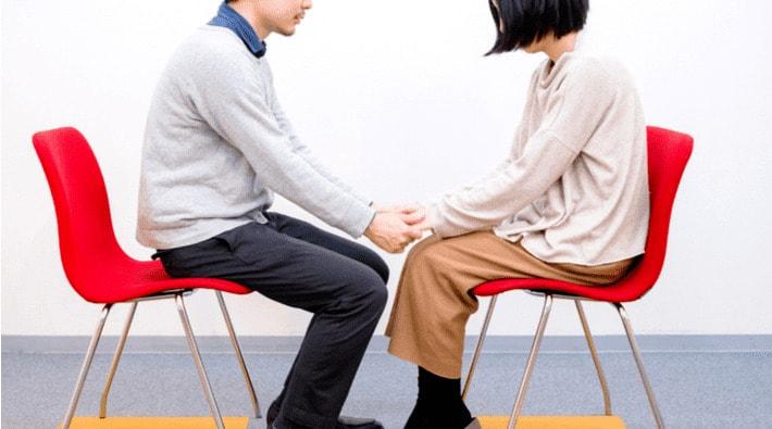 椅子に座り向かい合う男女