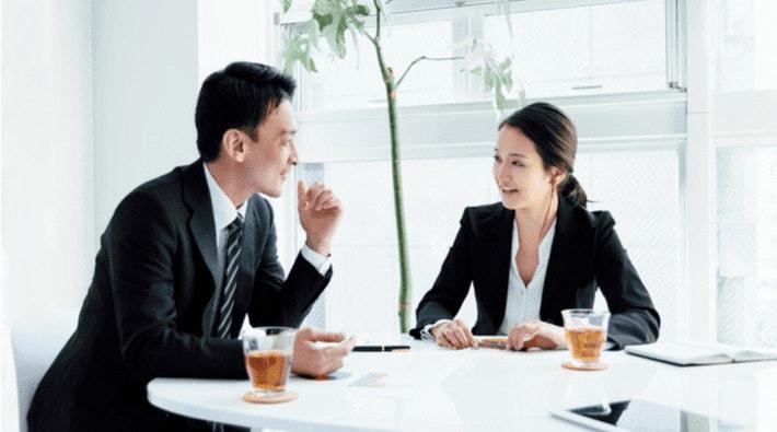 会議室で打ち合わせをする男女