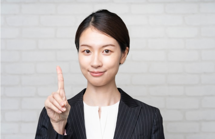 右手の人差し指を立てている女性