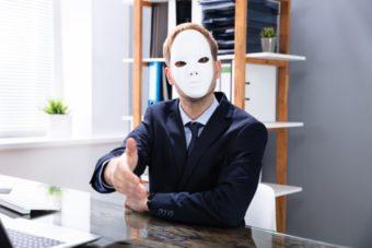 仮面を被り握手を求める怪しい男性