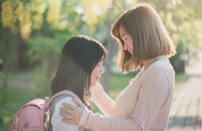 娘を笑顔で迎える母親
