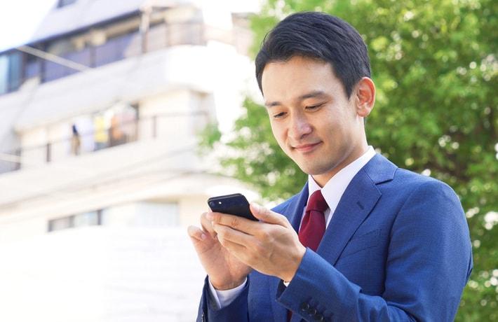 スマートフォンを操作するスーツ姿の男性