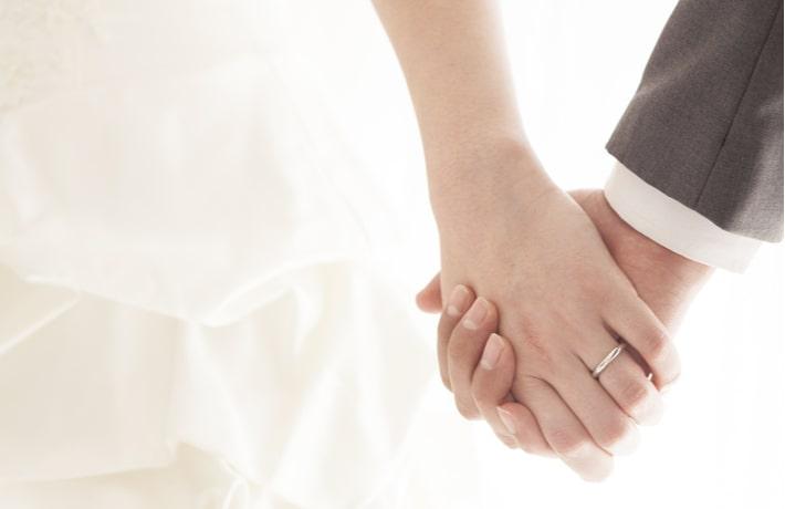 ウェディング姿で手を繋ぐ男女