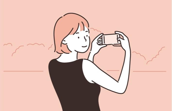 写真をとる女性のイラスト
