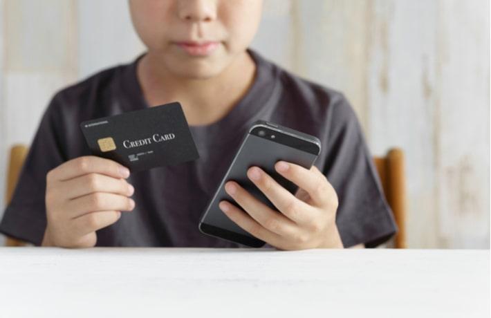 クレジットカードとスマトーフォンを持つ男性